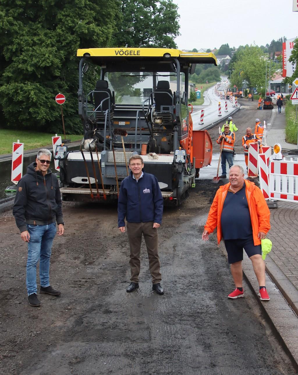 Die letzte Asphalt-Deckschicht wird gerade aufgebracht - dann ist die August-Balthasar-Straße fertig. Bürgermeister Peter Klär (Mitte) mit dem städtischen Tiefbauingenieur Daniel Fuchs (links) sowie Projektleiter Hans-Jürgen Schneider.